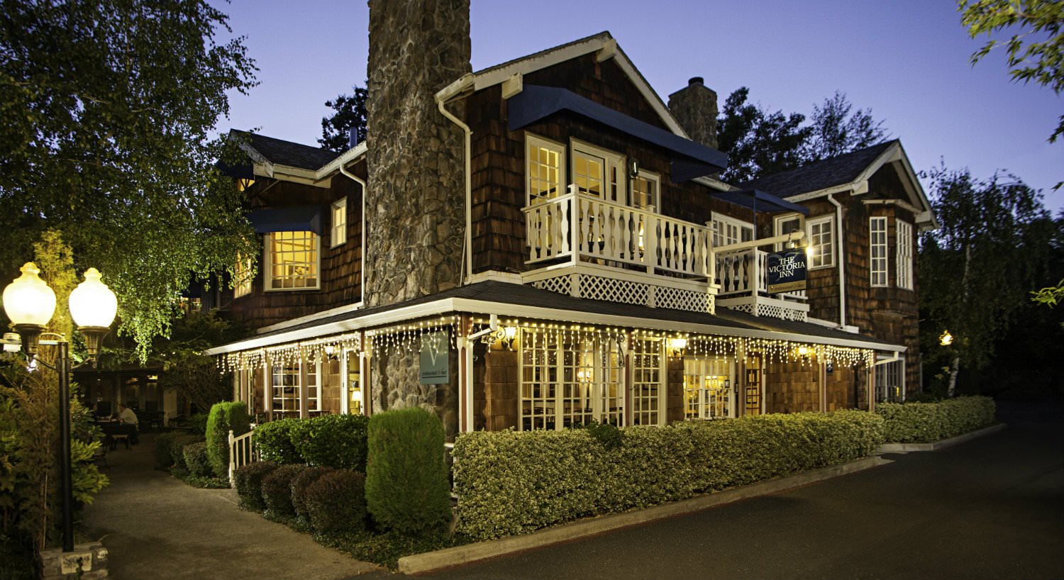 Exterior of inn at dusk with cedar shake siding and white trim, lit windows surrounded by trees and manicured shrubs
