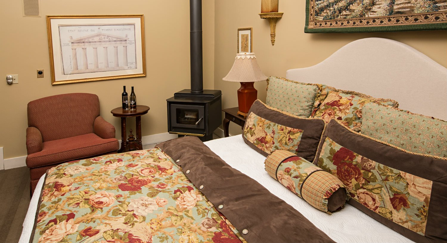 Bed with red, white, green, blue and brown floral comforter, tan walls, red chair with small table and wood stove