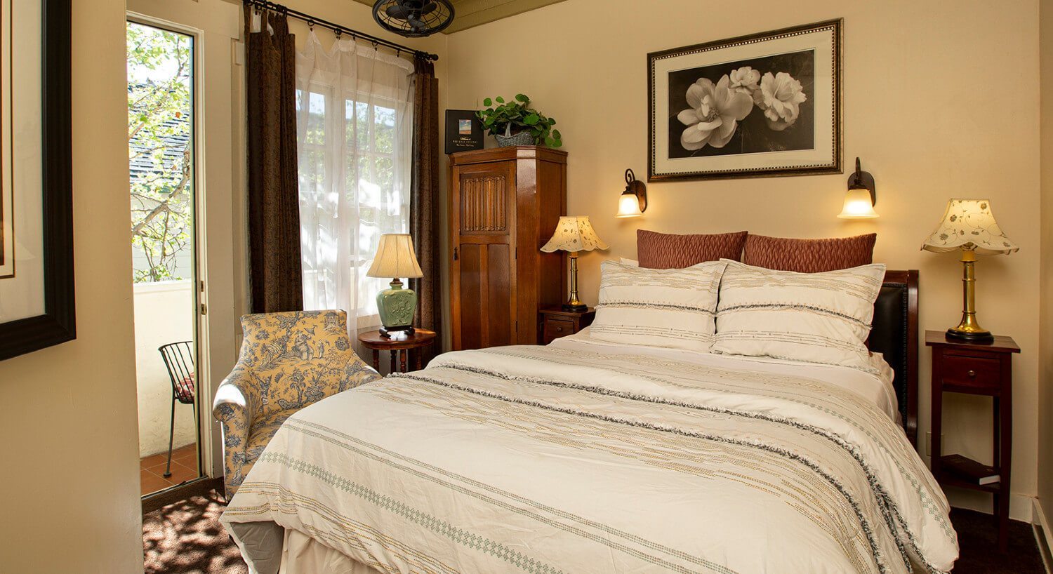 ivory bedroom with white comforter and pillow, picture over, three stands with lamps, brown curtains with sheer, hutch