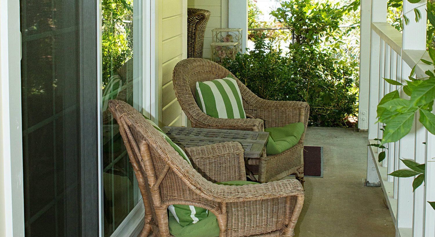 Covered patio with white railing, two wicker chairs with green cushions and green and white striped pillows