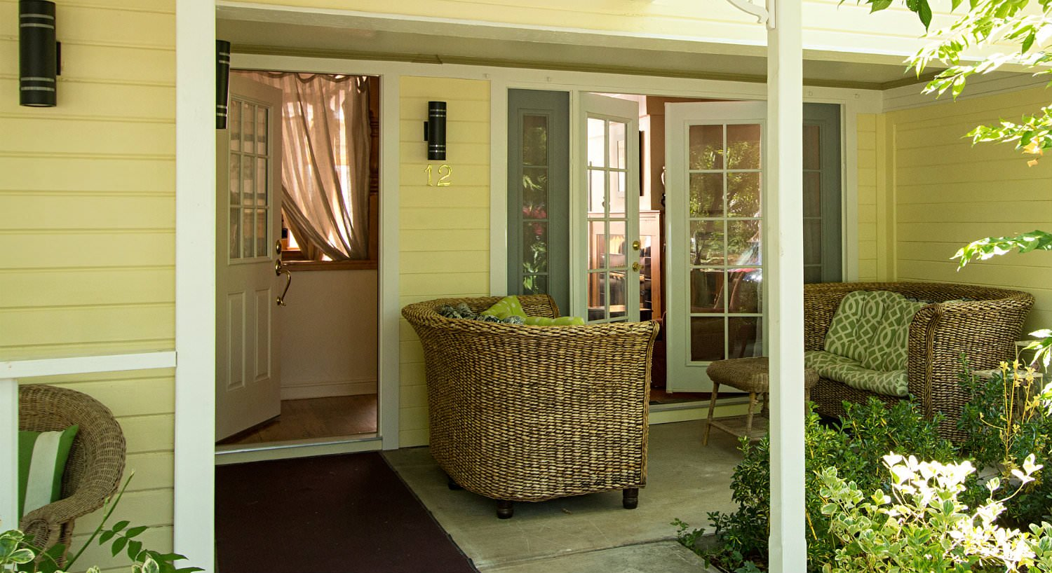 Covered patio with two wicker loveseats with green and white cushions in front of a partially open French door