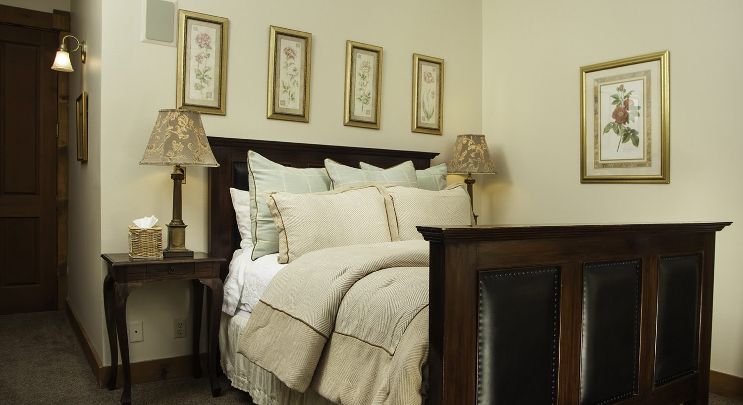 Dark wood and leather bed with ivory comforter, light green and ivory pillows, gold-framed pictures, and nightstands with lamps