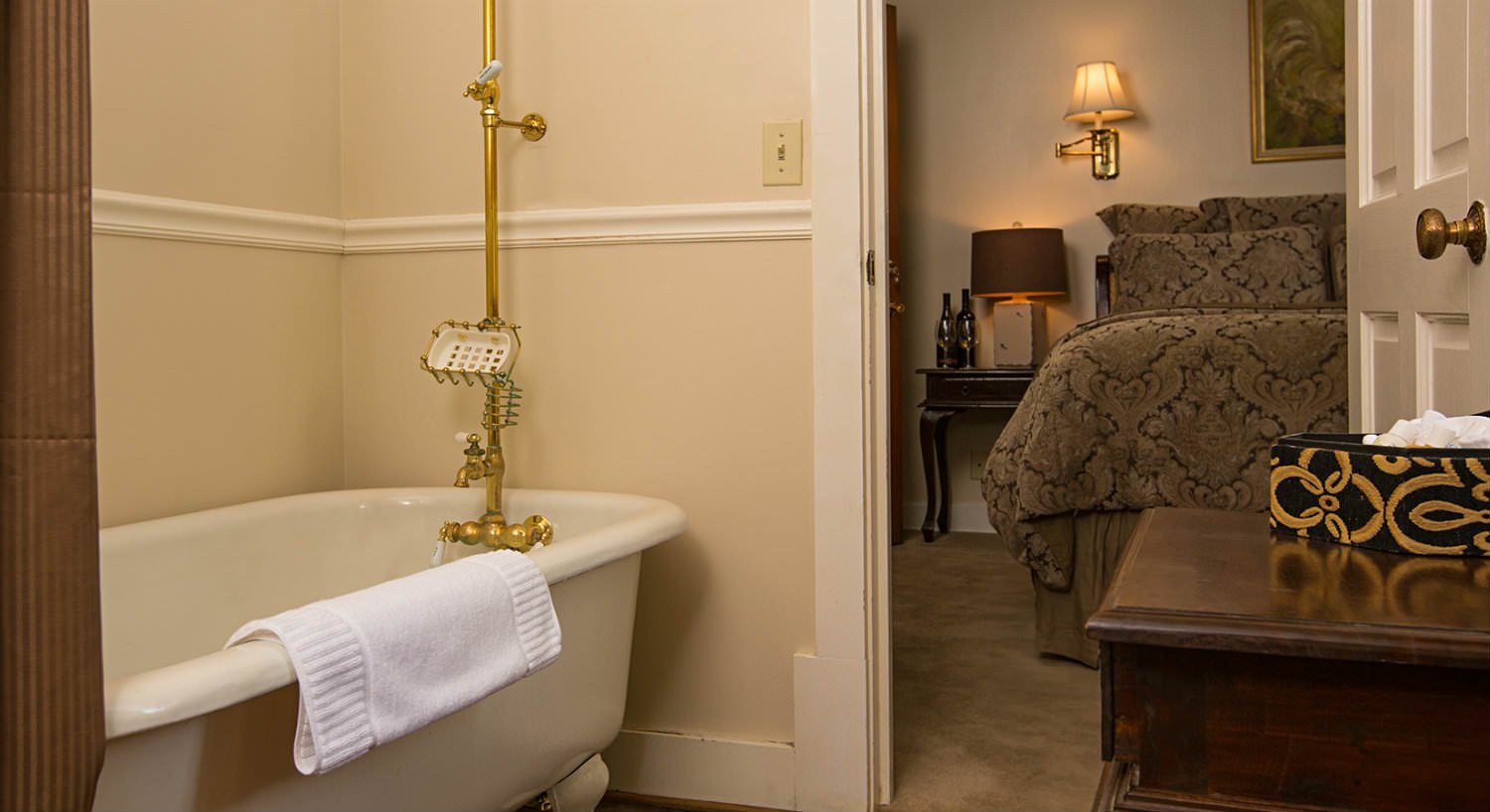 Clawfoot tub with brass faucet, ivory walls, bed in the background with brown and black comforter and dimly lit sconce