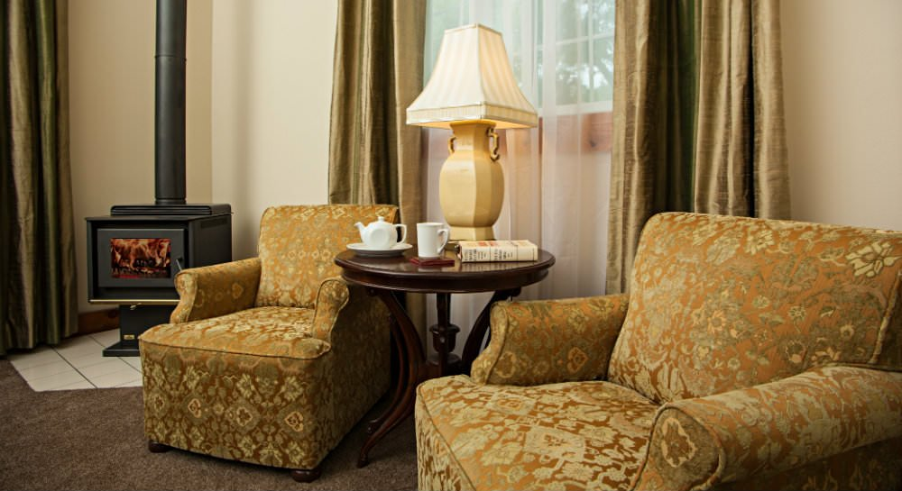 Two gold upholstered chairs flanking a small round table with ivory lamp and a black wood stove