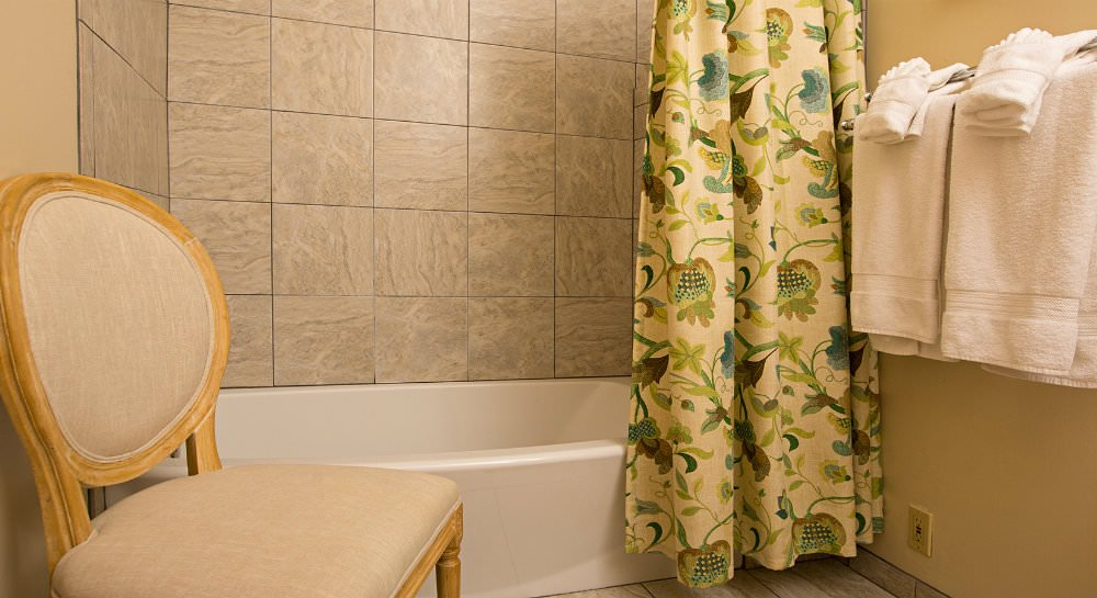 Bathtub with tiled surround, an ivory, green and blue shower curtain, small wood and upholstered chair with white towels
