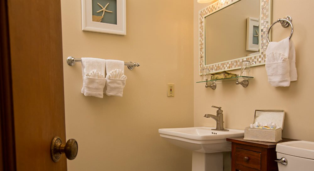 Ivory bathroom with white pedestal sink, shimmery framed mirror, a box of toiletry samples and white towels