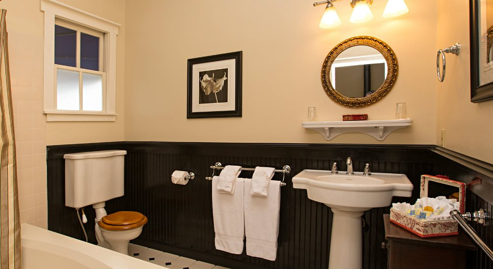 Bathroom with black beadboard topped with ivory walls, white pedestal sink with mirror, tile floors and small window