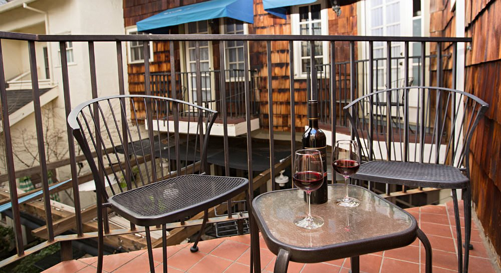 Red tiled balcony with black metal railing and chairs and table with wine bottle and two glasses of red wine