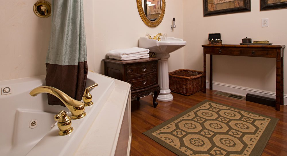 Bathroom with wood floors, white tub and brass faucet, white pedestal sink and brass oval mirror