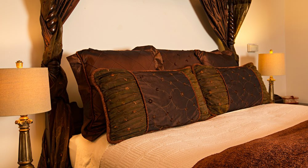 Close up of dark wood four poster bed with brown pillows, ivory blanket and brown bedspread, and nightstand with lamp