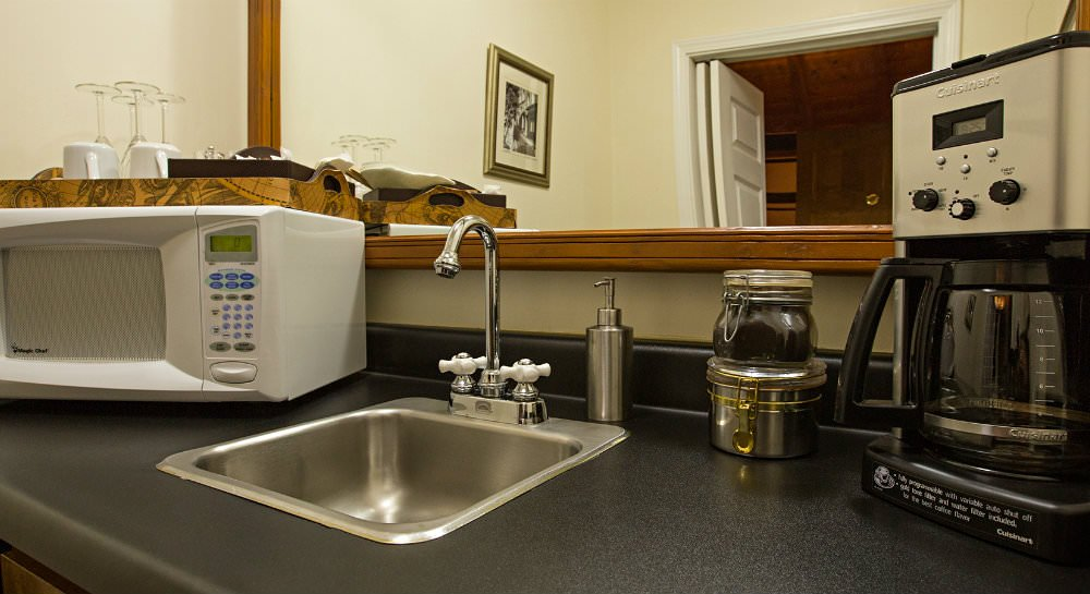 Dark countertop with stainless steel sink and coffee pot and tray with coffee mugs and wine glasses on white microwave