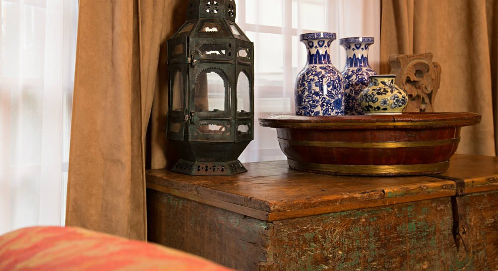 Old wooden chest with antique vases and lantern in front of a window with white sheers and tan curtains