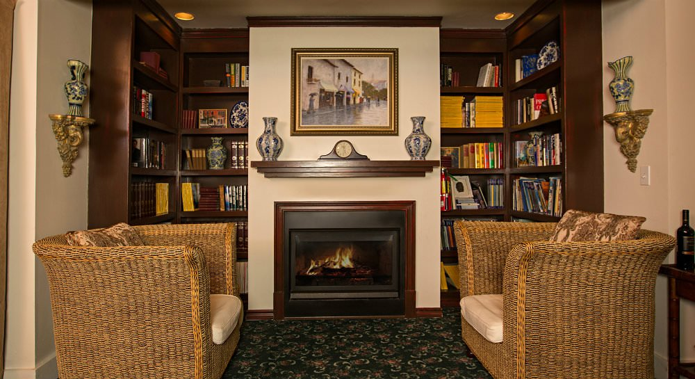 Charming nook with dark wood bookshelves flanking an fireplace with two wicker loveseats on a dark green floral rug