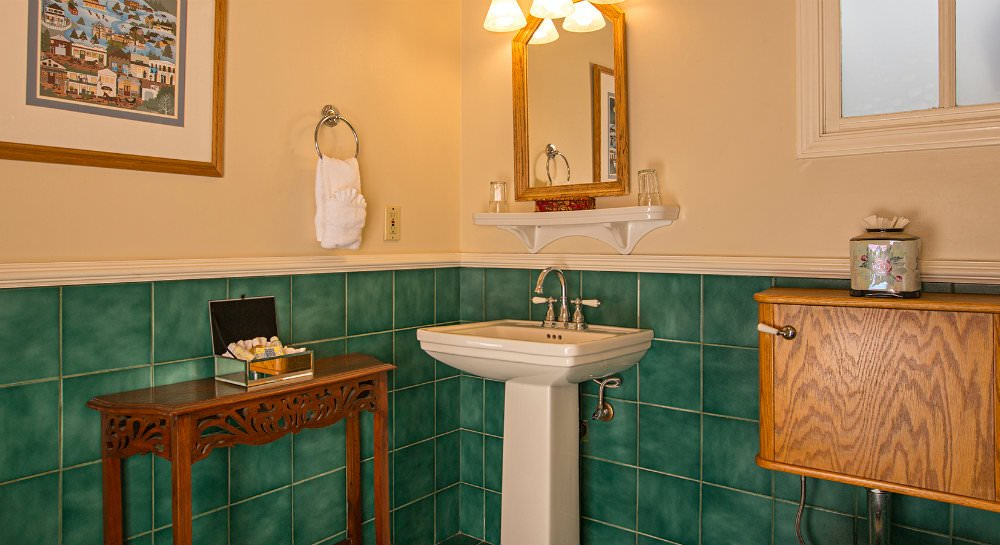 Bathroom with green tiled walls topped with ivory painted walls, white pedestal sink with mirror and small window