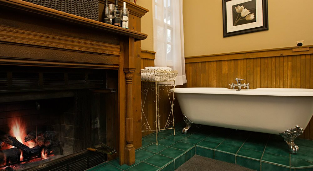 Close up of a fireplace with glowing flames, a white clawfoot tub, and wood paneling topped with gold painted walls