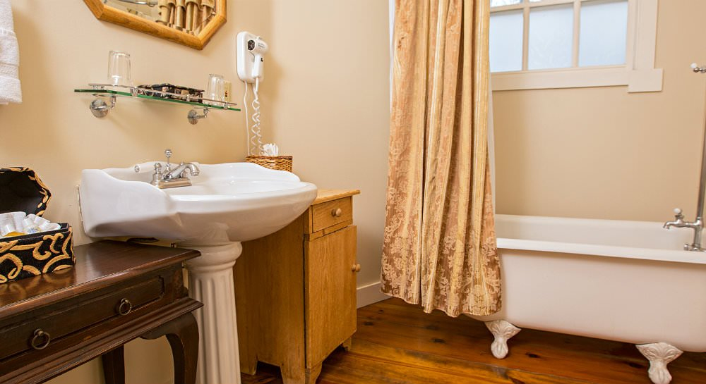 White clawfoot tub with gold curtain, window with privacy glass, white pedestal sink with framed mirror and table with toiletries