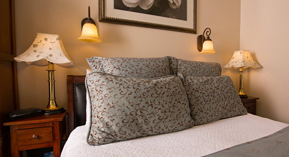 Close up of bed with light blue and brown pillows, matching nightstands and lamps, floral print and sconces over bed
