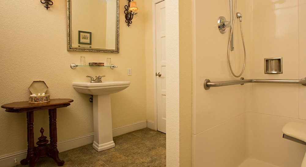Ivory bathroom with white pedestal sink, metal framed mirror, shelf with two glasses and wood table with toiletry samples