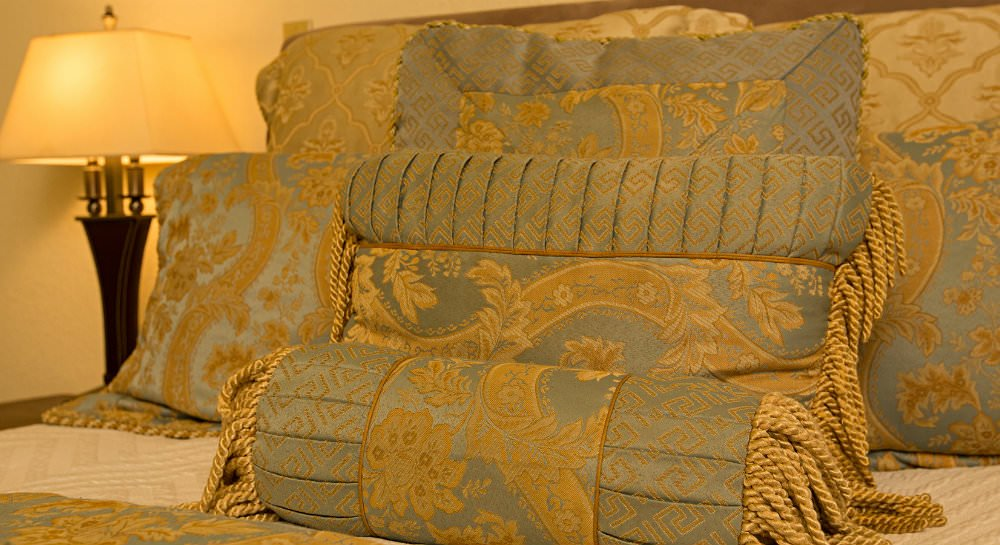 Close up of bed with light blue and gold pillows, ivory walls and a nightstand with lamp