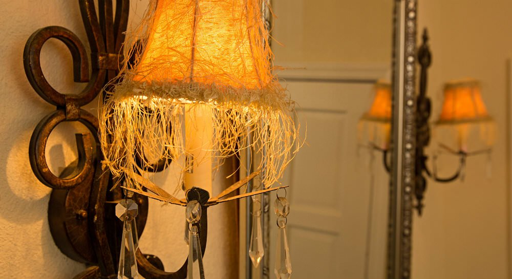 Close up of bronze metal wall sconces with fringed lamp shades flanking metal framed mirror
