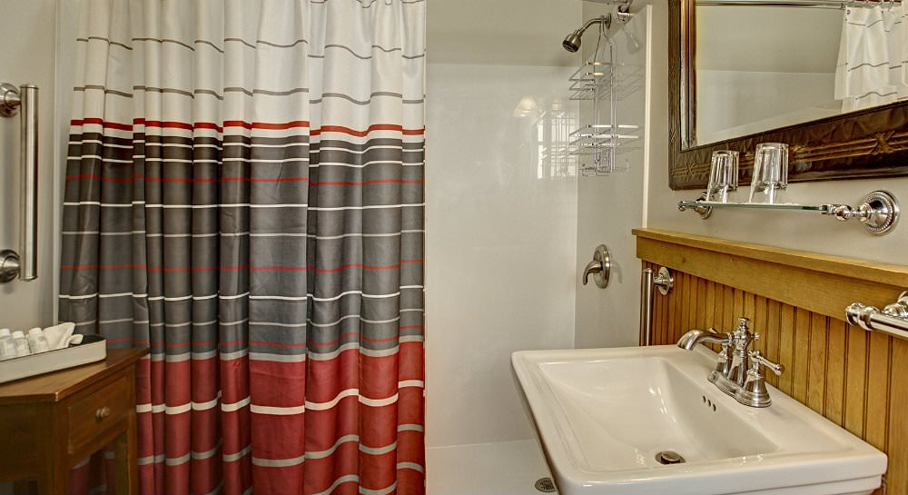 White shower surround with red grey and white striped shower curtain, white pedestal sink with mirror and glass shelf
