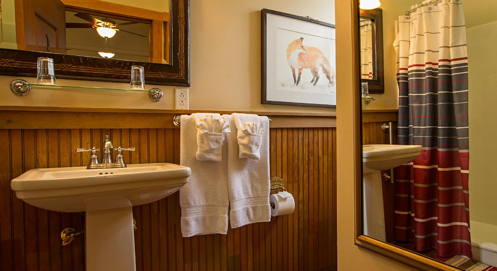 White pedestal sink, wood paneling topped with ivory walls, framed mirror, glass shelf with two glasses and white towels2