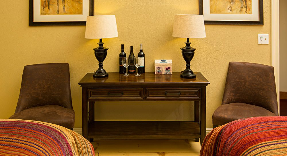 Two brown chairs flanking a wood console with two lamps, three wine bottles and two glasses and warm beige walls