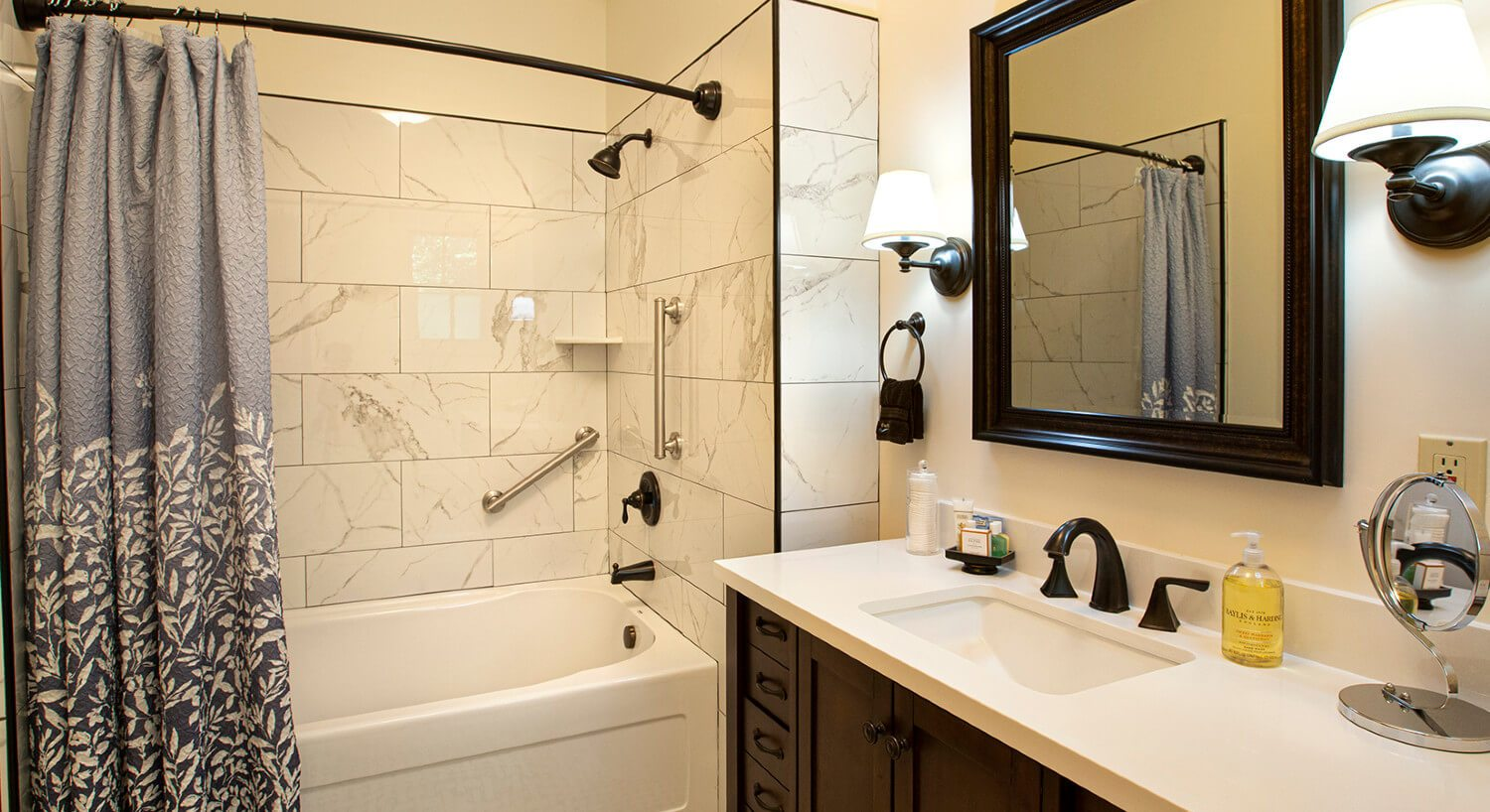 Ivory bathroom with white tiled tub and shower, white and gray shower curtain and white pedestal sink