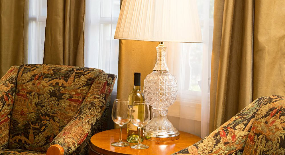 Close up of round wood table with lamp, white wine bottle and two wine glasses flanked by richly upholstered chairs