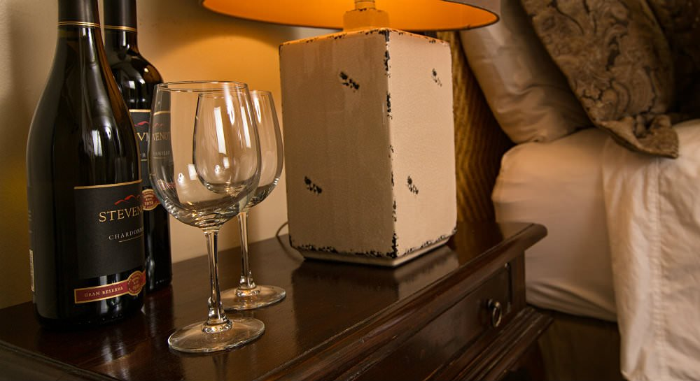 Close up of dark wood nightstand with two wine bottles and two wine glasses and a dimly lit lamp