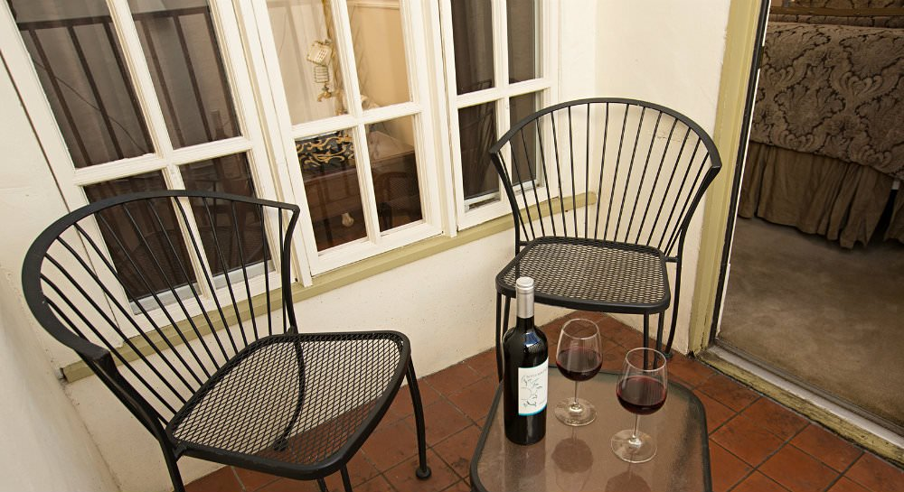 Balcony with red tile floor, two black metal chairs, small table with wine bottle and two glasses of red wine