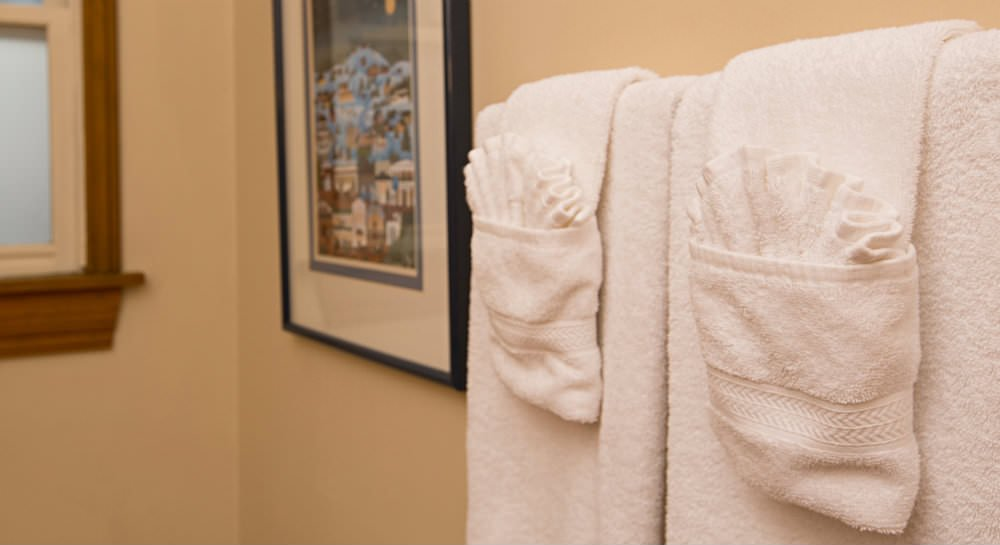 Close up of white towels on towel bar, ivory walls, and framed picture and window in background