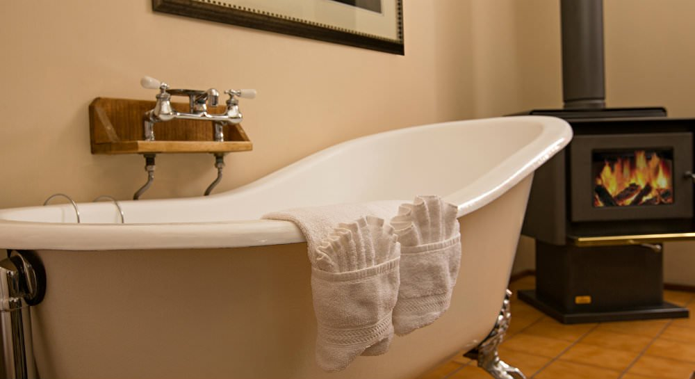 Close up of white clawfoot tub, ivory walls, and black cast iron wood stove in background
