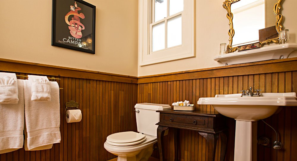 White pedestal sink, brass mirror, white shelf with two dirnking glasses, toiletry samples on wood table and bed in background