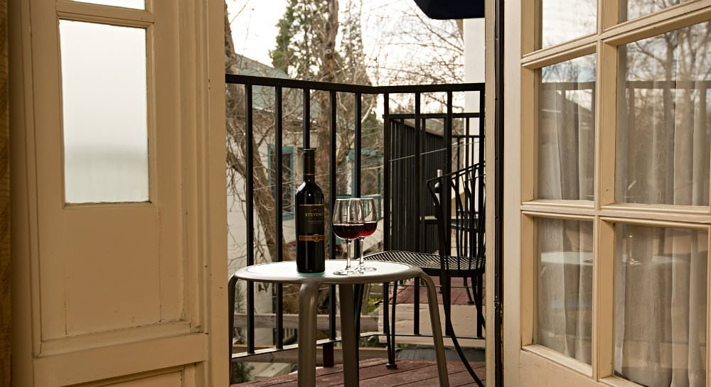 French door open to balcony with black metal railing and chair, table with wine bottle and two glass red wine