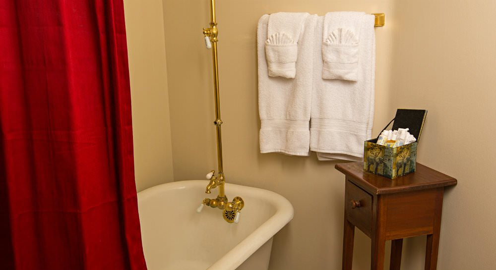 Close up of white clawfoot tub, brass antique faucet, red shower curtain, wood table with toiletries and white towels