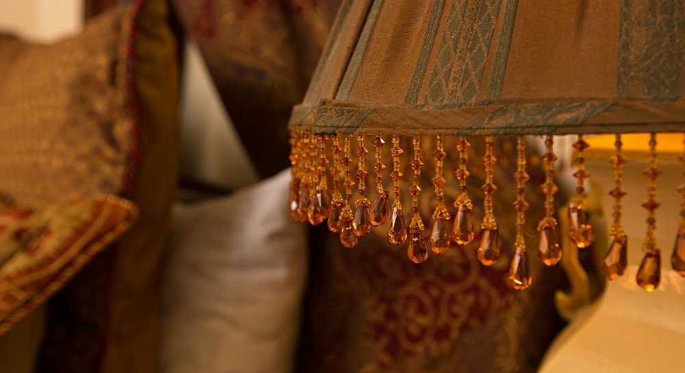 Close up of brown and green lamp shade with hanging amber beads and bed in background