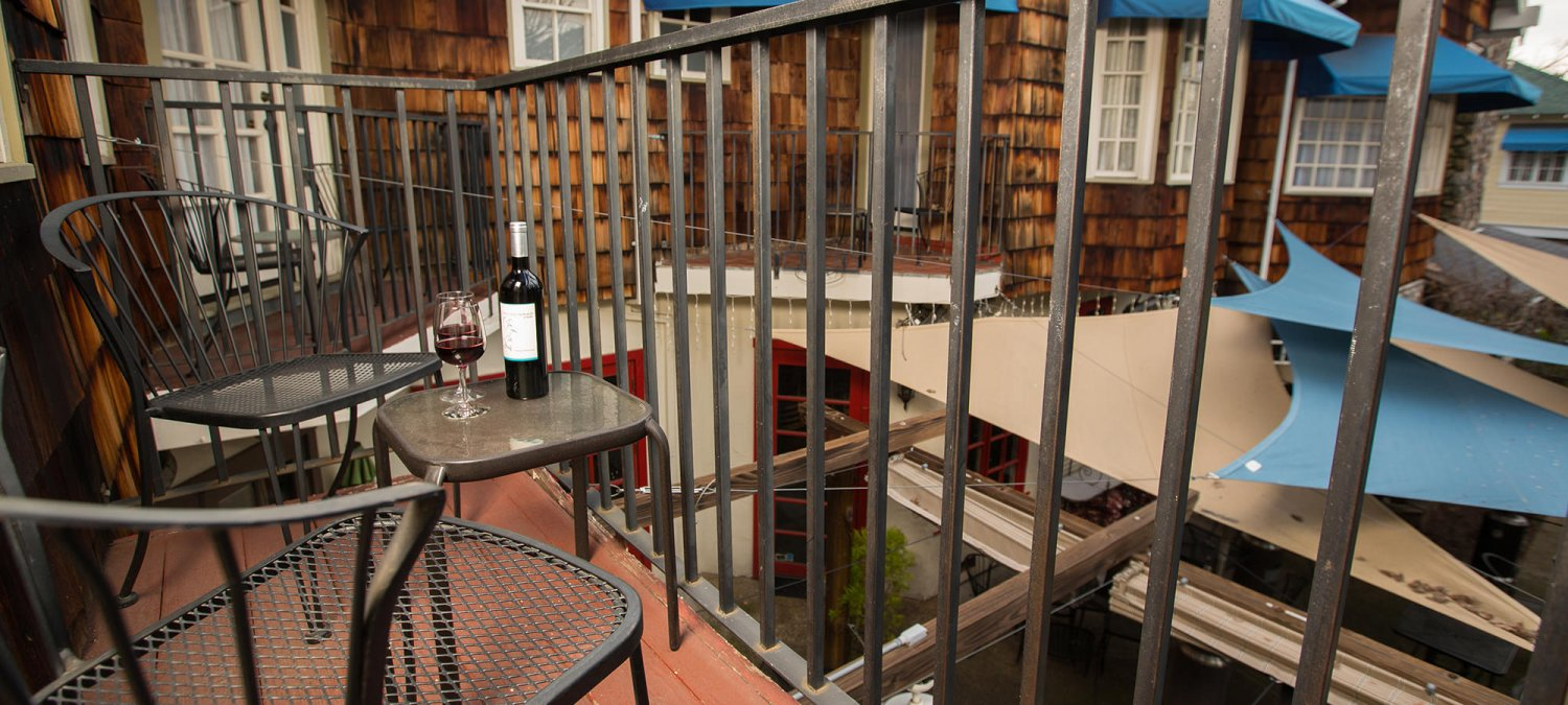 Balcony with black metal railing, two black metal chairs and table with wine bottle and two glasses of red wine