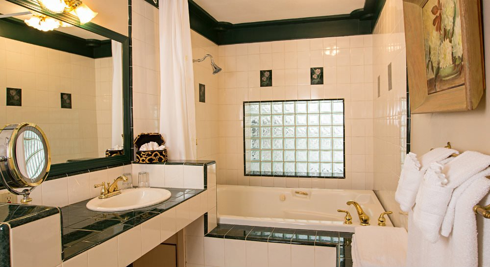 White and green tiled tub, shower and sink with glass block privacy window, brass fixtures and white towels