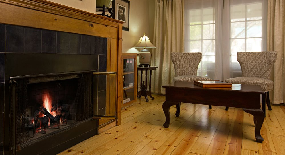 Fireplace with black tile and wood mantel surround, light wood floors, two chairs and coffee table in front of window