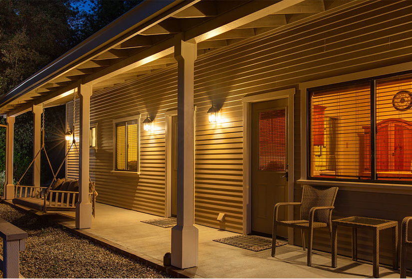 Night time view of cottage entry and through window, with porch swing hanging near the door.
