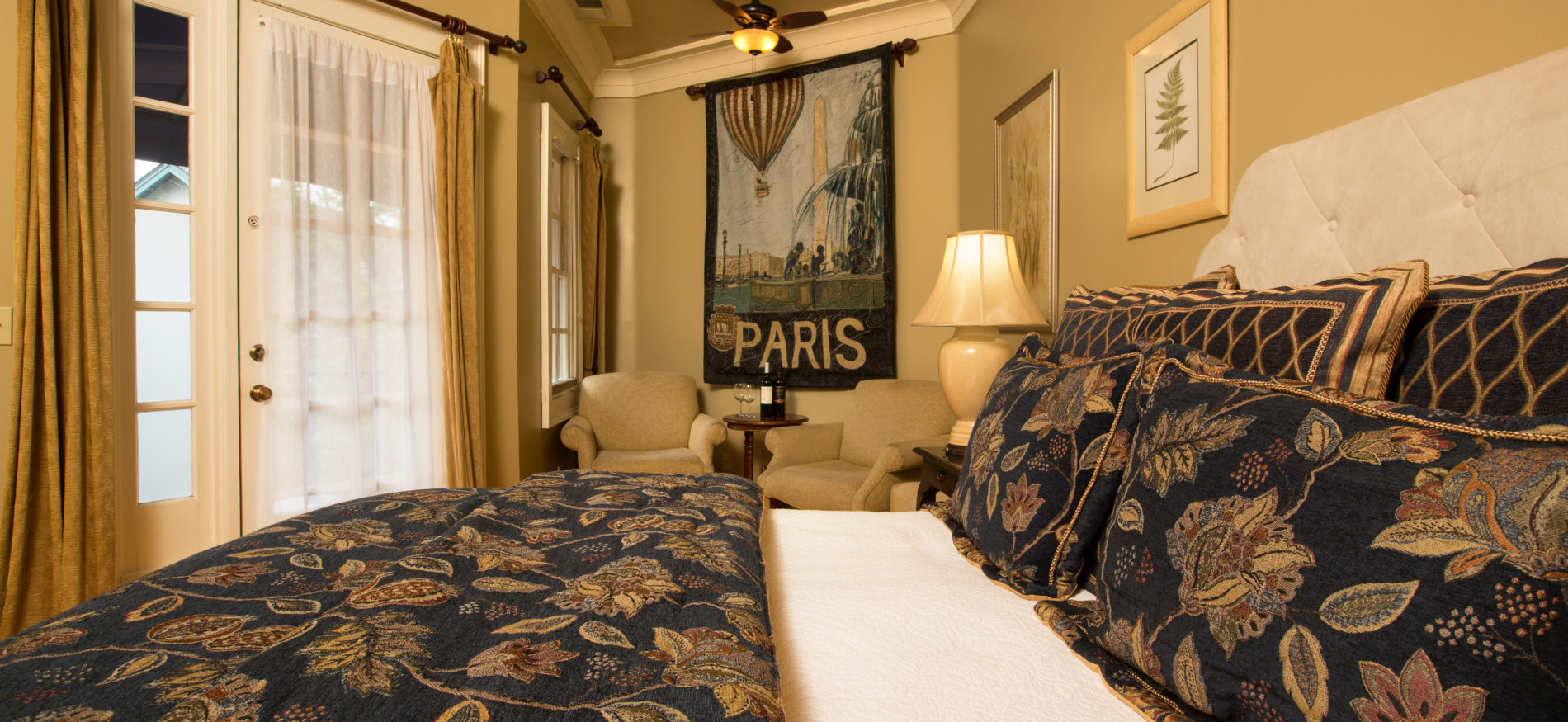 Cream and yellow guestroom with close up of the black and gold paisley bedspread with Paris tapestry on wall