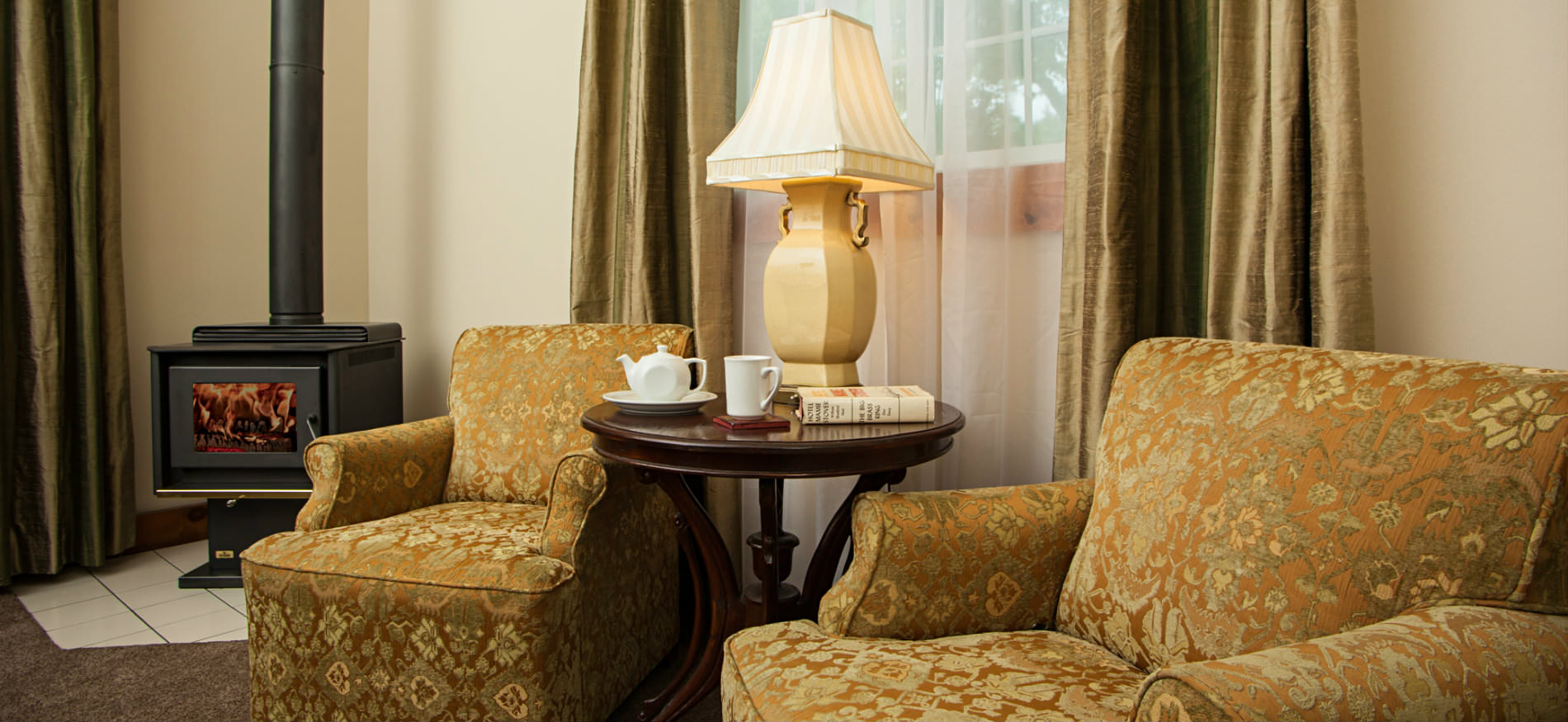 Two gold upholstered chairs flanking a small round table with ivory lamp and a black woodstove