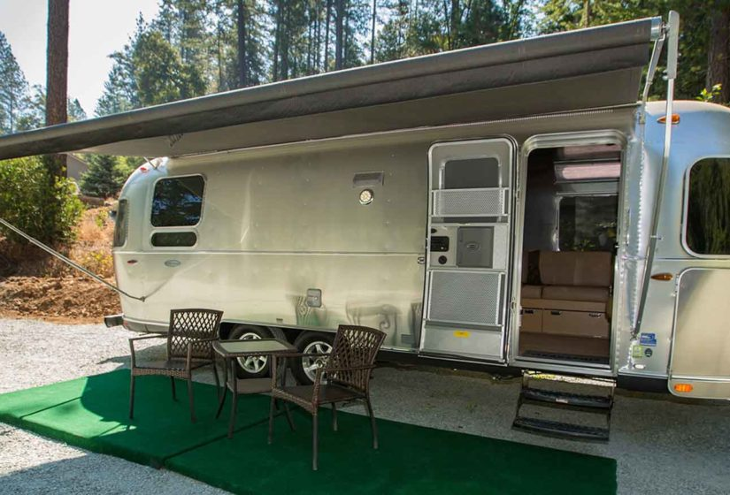 An outdoor bistro set sits on green astroturf in front of the old metal airstream rv