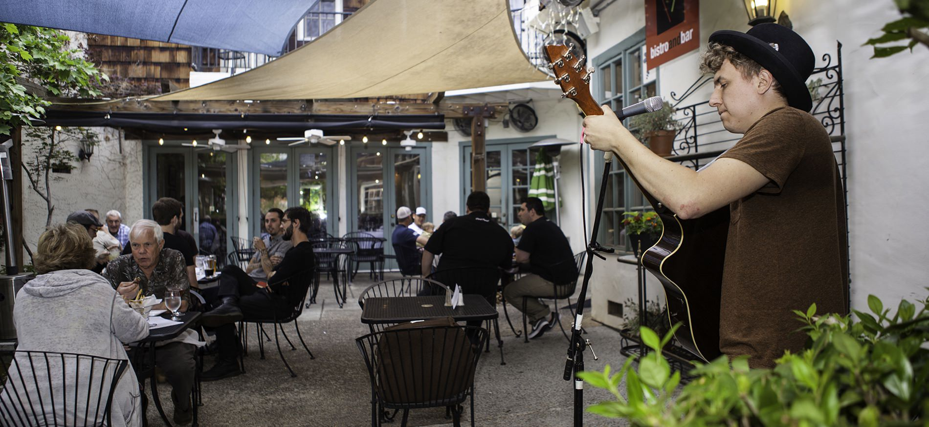 People sitting at black metal tables eating and talking outside a bistro and bar with live musician playing guitar