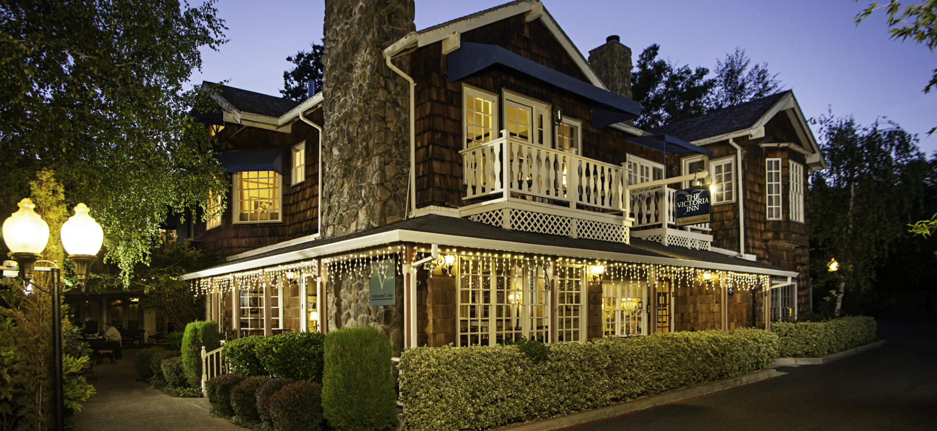 Victoria Inn exterior at dusk with warmly lit windows surrounded by lush green trees and manicured shrubs