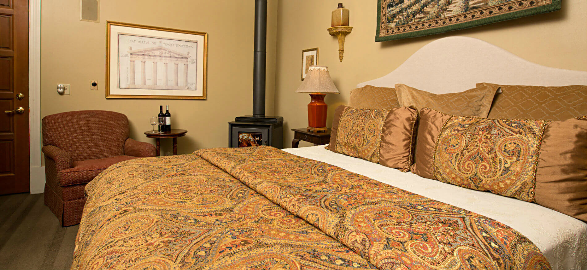 Bed with gold, blue, red, brown paisley pattern comforter, tan walls, red chair with small table, and wood stove
