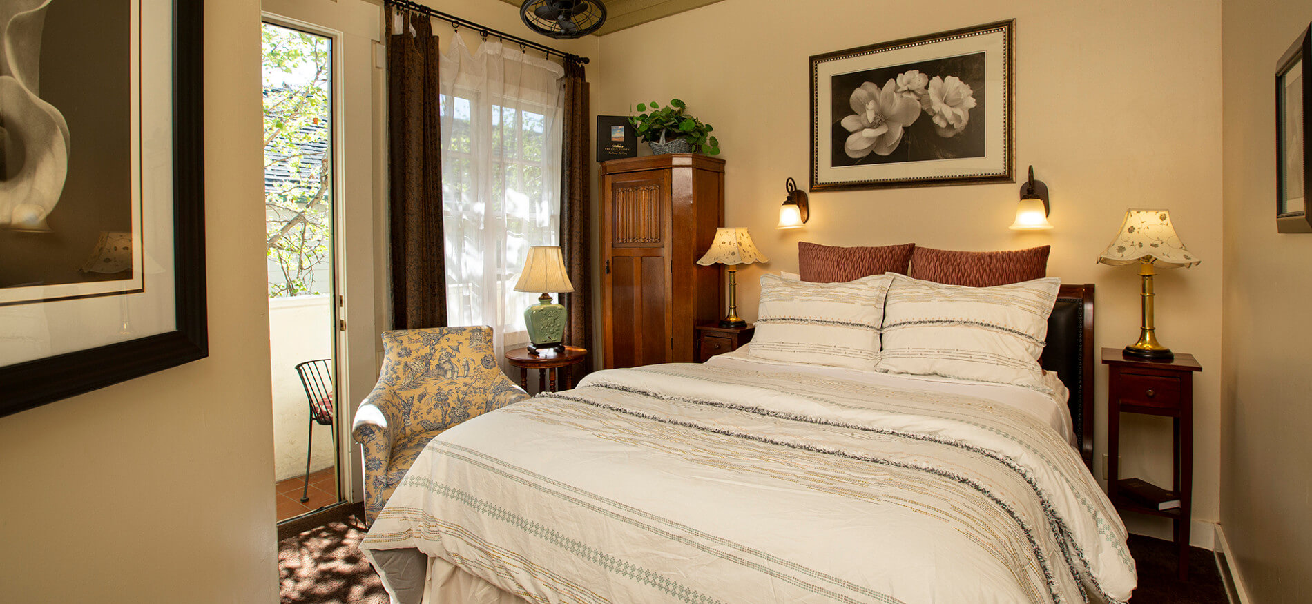 Bed with light blue and brown comforter, ivory walls, floral picture and two sconces over bed, two nightstands with lamps