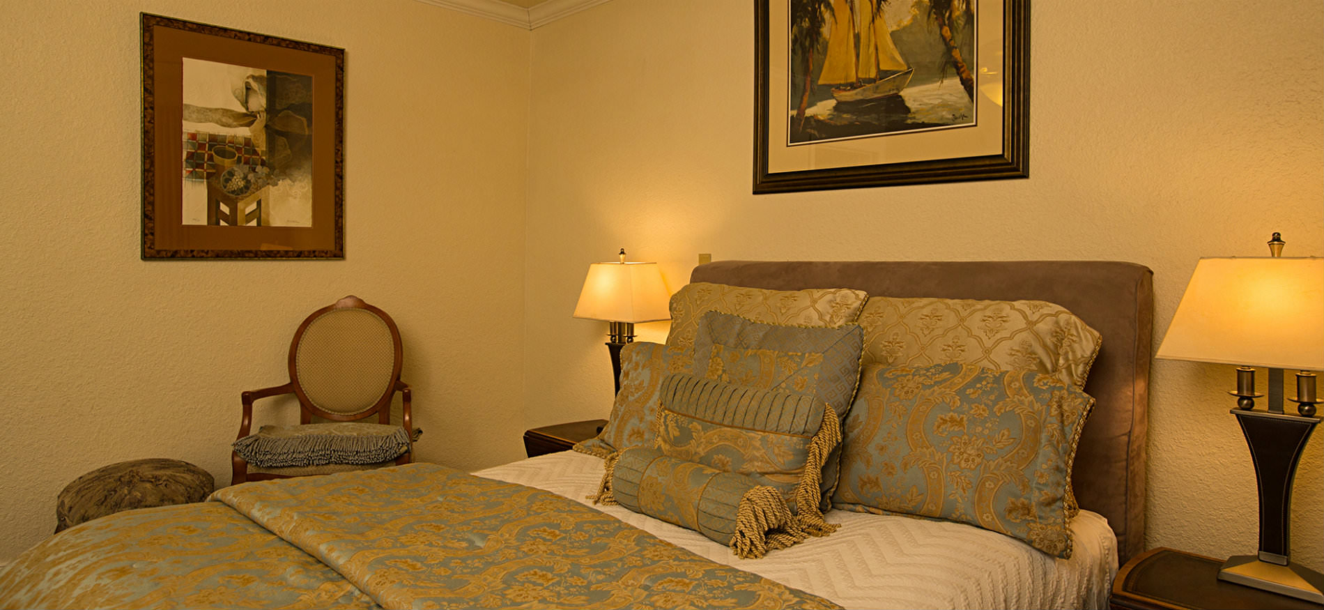 Bedroom with upholstered headboard, gold and light blue comforter, textured ivory walls, and two nightstands with lamps