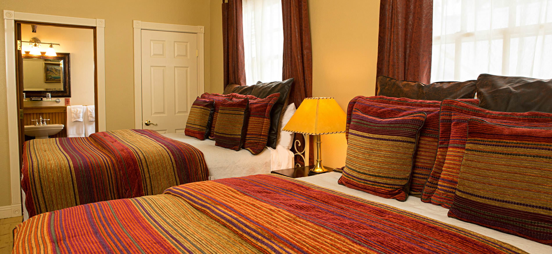 Bedroom with two beds covered in red and gold striped bedspreads, a nightstand, and two large windows
